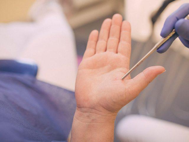 Zahnärztin demonstriert die schonende Behandlung auf der Hand eines Patienten.