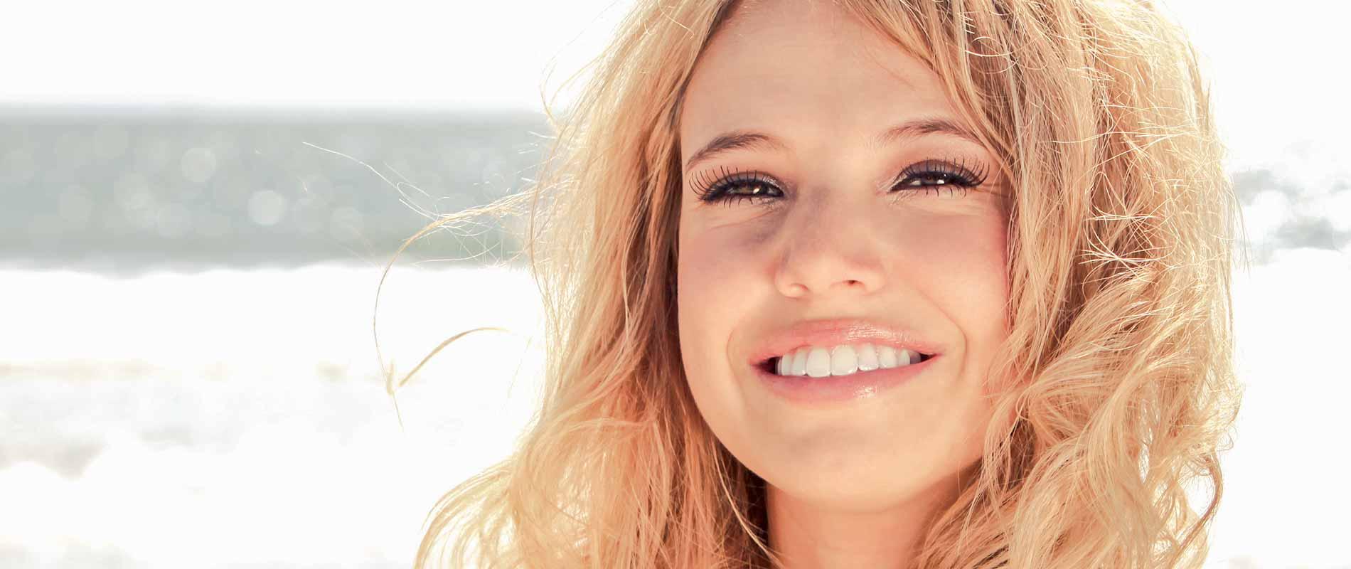 Junge Frau mit weißen Zähnen lächelt in die Kamera.