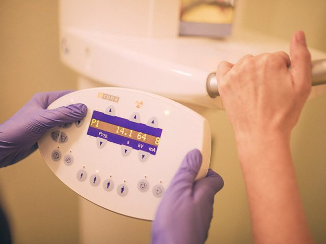 Zahnarzthelferin bereitet Röntgengerät zur Aufnahme vor.
