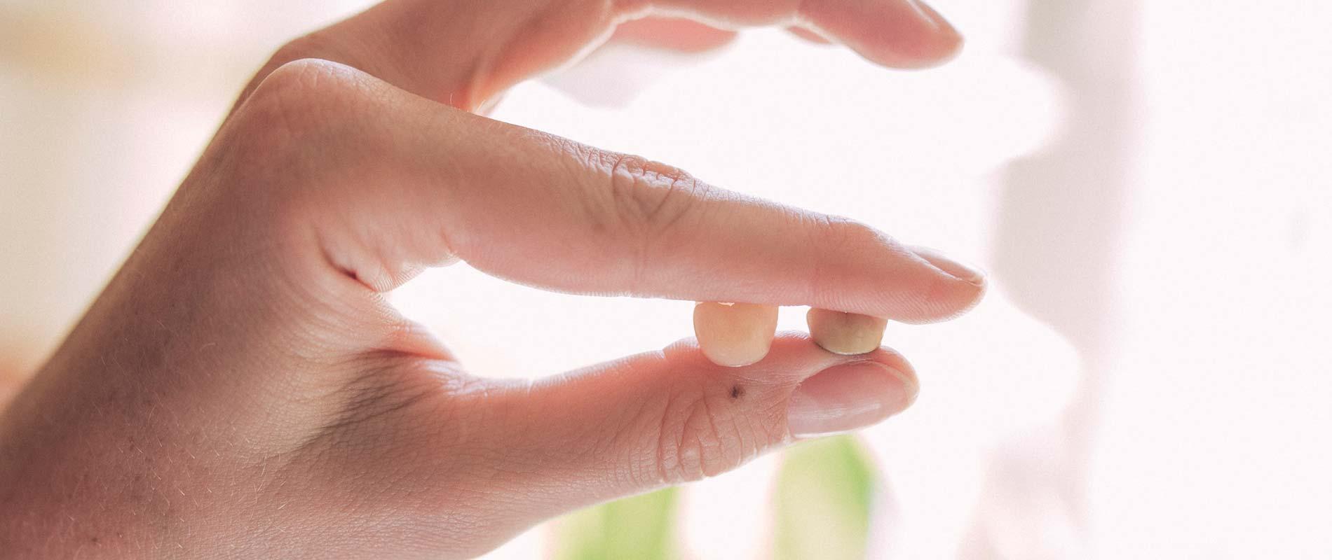 Zahnärztin hält Kronen für Zahnersatz in der Hand.